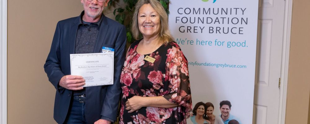 Andy McKee of Big Brothers Big Sisters accepts grant from CFGB Board member, Martha Pedoniquotte